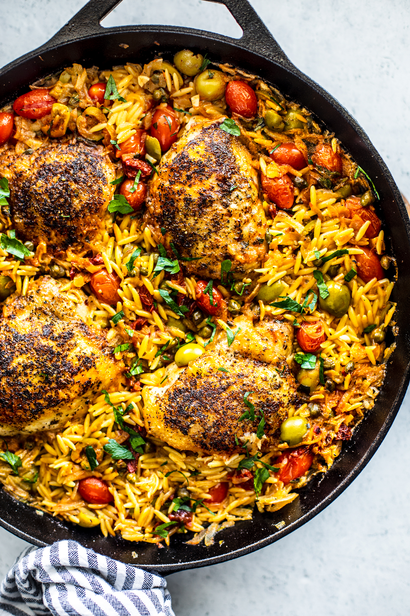 Overhead shot of skillet with orzo, crispy chicken, and veggies.
