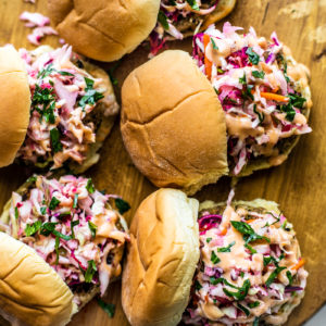 Wooden serving platter with fish sliders topped with slaw.