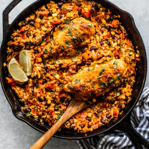 Skillet full of cooked rice and cheesy chicken, with a spatula digging in.