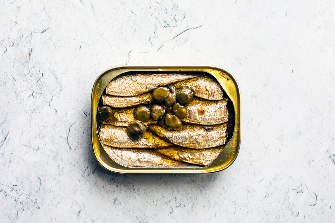 Opened can of sardines with capers on top.