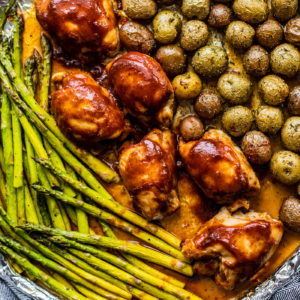 Roasted asparagus, baby potatoes, and BBQ chicken on a sheet pan.