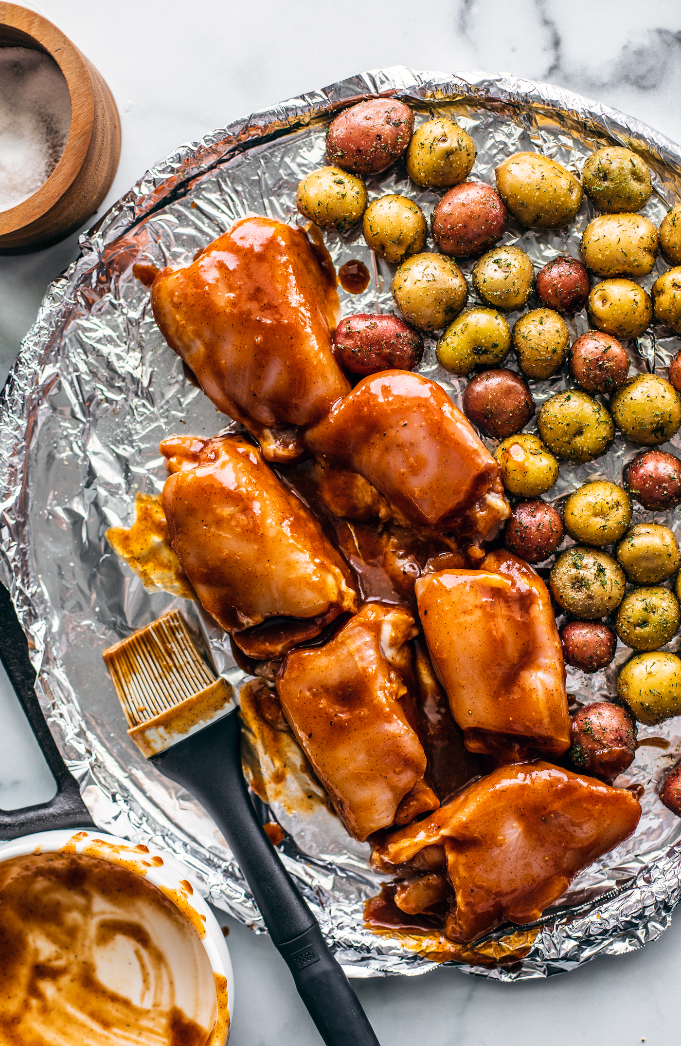 Uncooked chicken and potatoes on sheet pan with BBQ sauce.