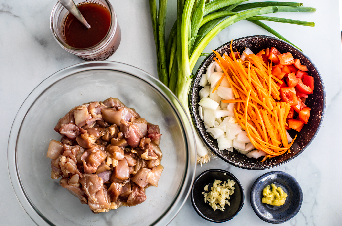 Bowl of marinated chicken, jar of sweet and sour sauce, bowl of vegetables, garlic, ginger, and scallions.