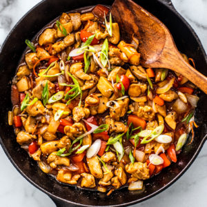 Skillet full of sweet and sour chicken with peppers and onions.