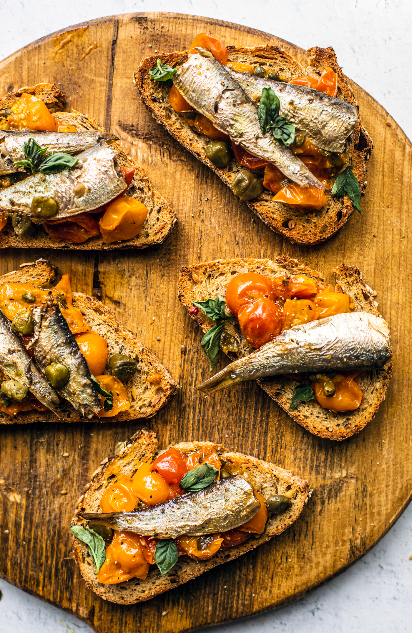 Wooden serving board with toasts topped with tomato confit and sardines.