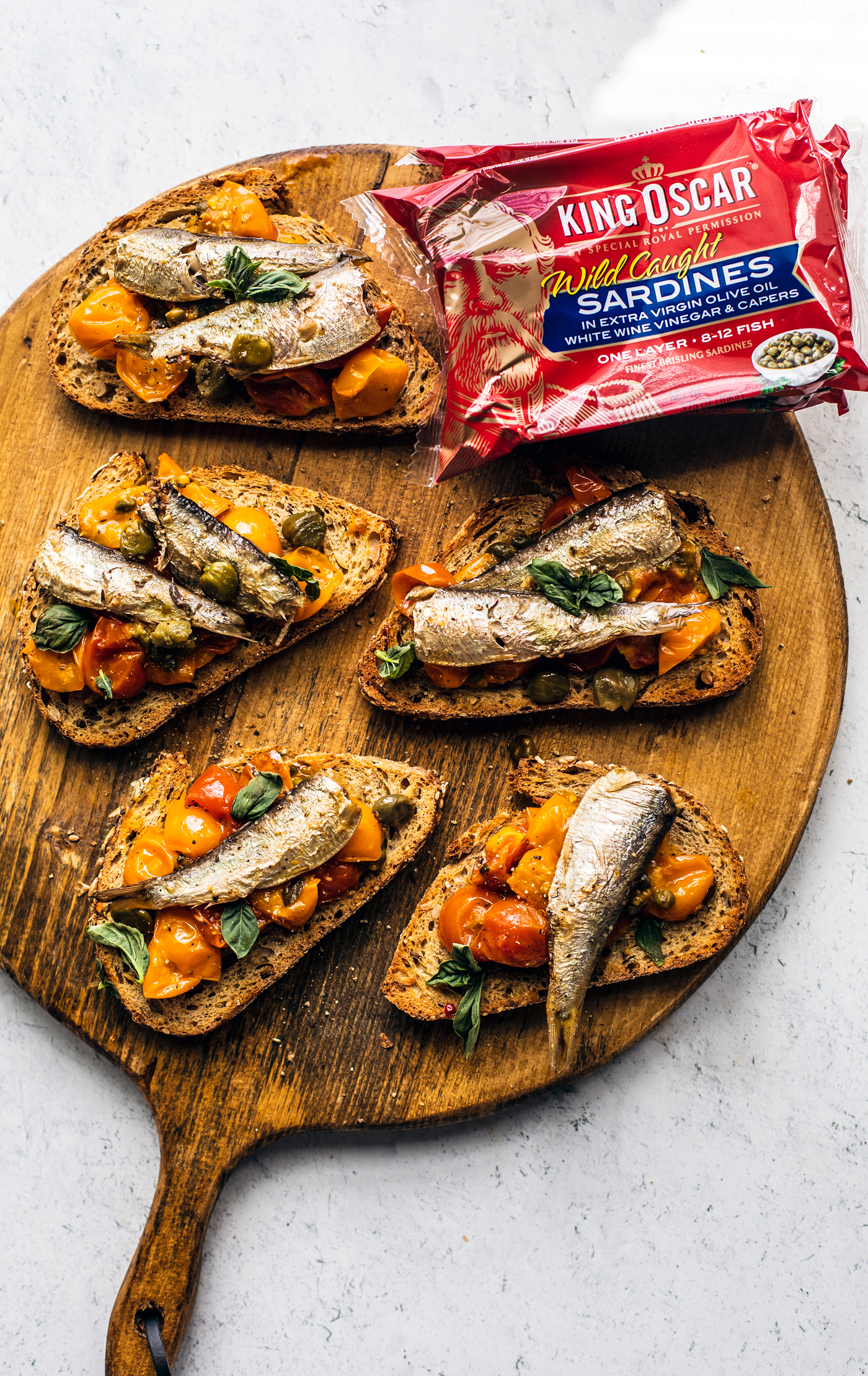 Toasts topped with tomato confit and sardines on wooden serving board.