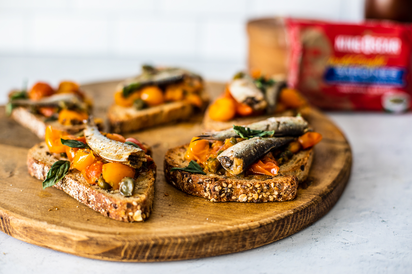 Close up of tomato confit on toast with sardines, laid out on wooden serving board.
