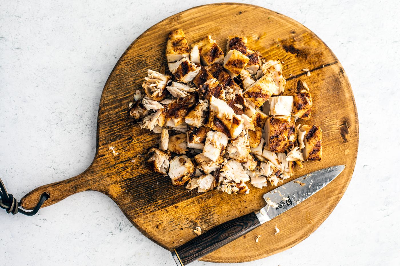 Chopped mahi-mahi on round cutting board.