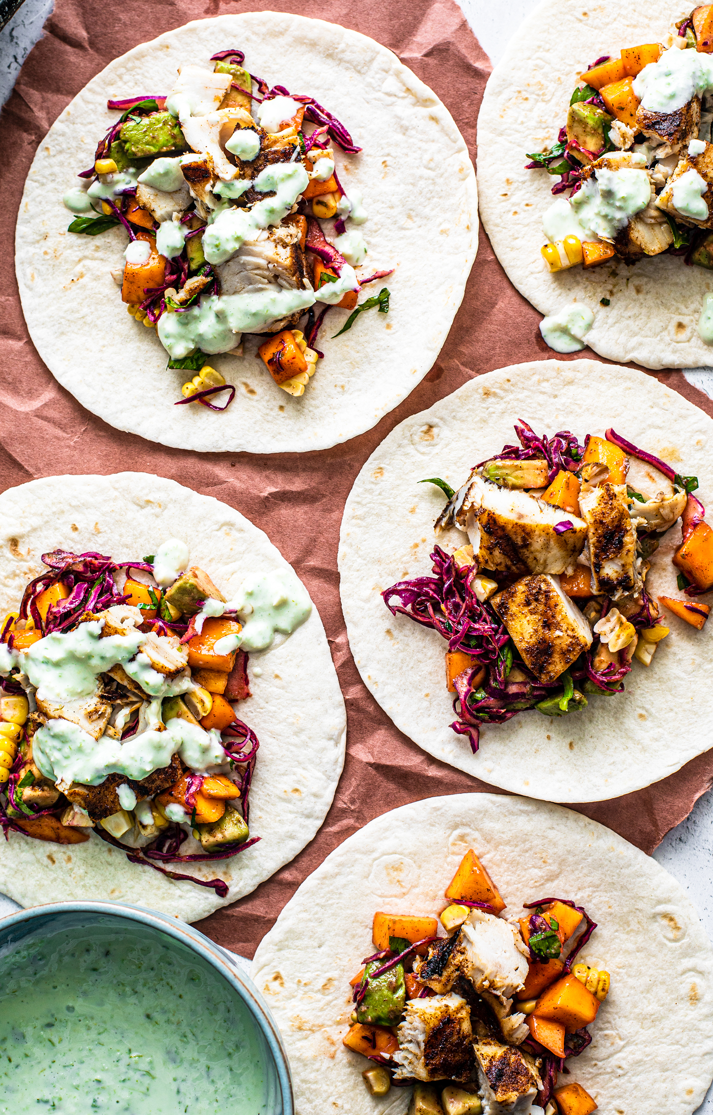 A flatlay of colorful fish tacos, some drizzled with jalapeno sauce.