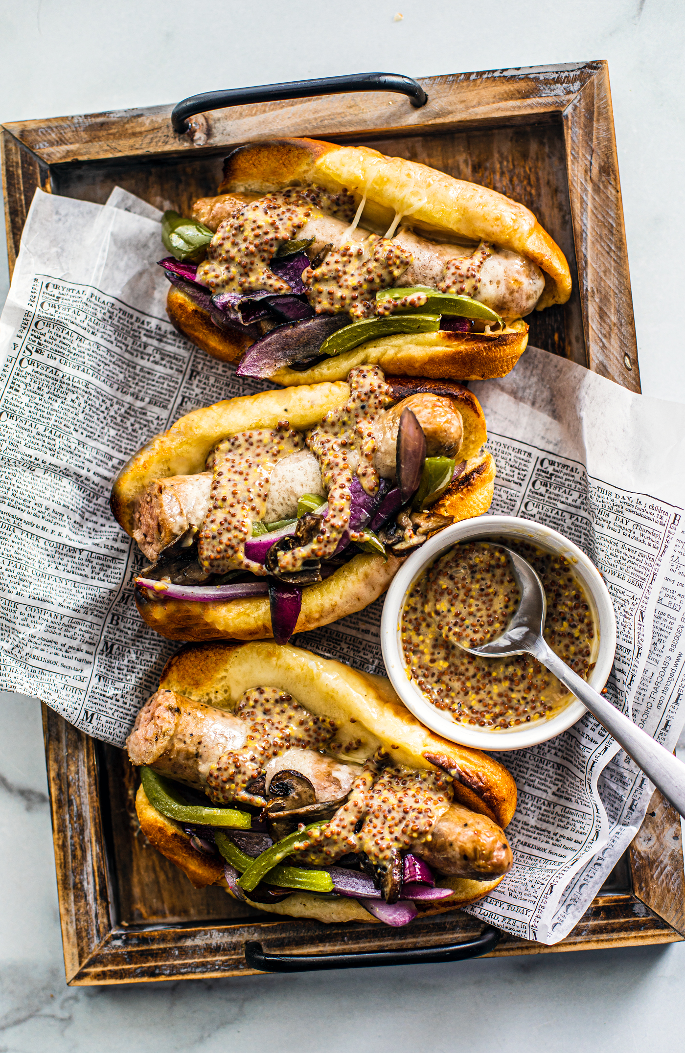 Three buns stuffed with sausage and peppers on a tray with a small bowl of mustard