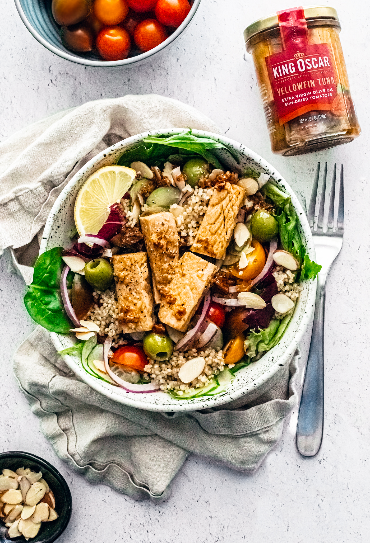 Big bowl full of mixed greens topped with quinoa, tomatoes, olives, cucumbers, almonds, and large chunks of tuna next to glass jar of King Oscar tuna.