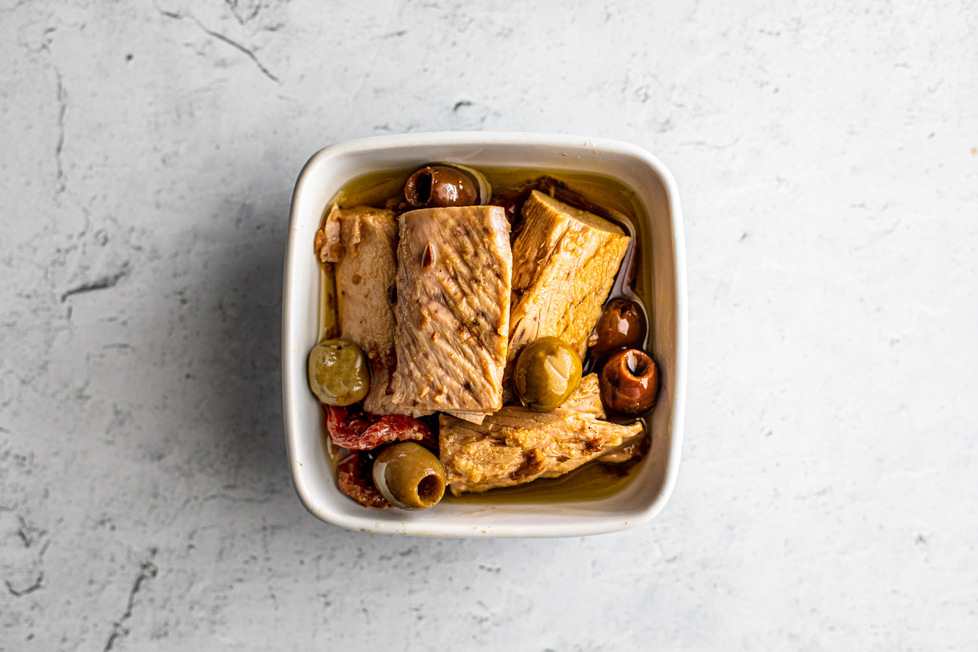 Overhead shot of big tuna fillets in a small serving dish with green and kalamata olives, oil, and sun-dried tomatoes.