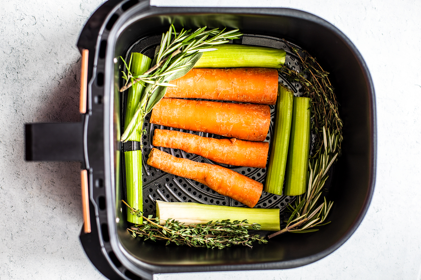 Air fryer basket with carrots, celery, and leeks cut into planks.