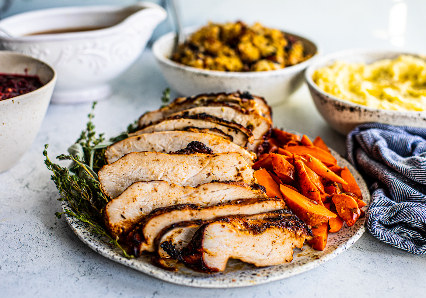 Close up side shot of sliced turkey breast on serving platter with serving bowls of holiday sides blurred in background.
