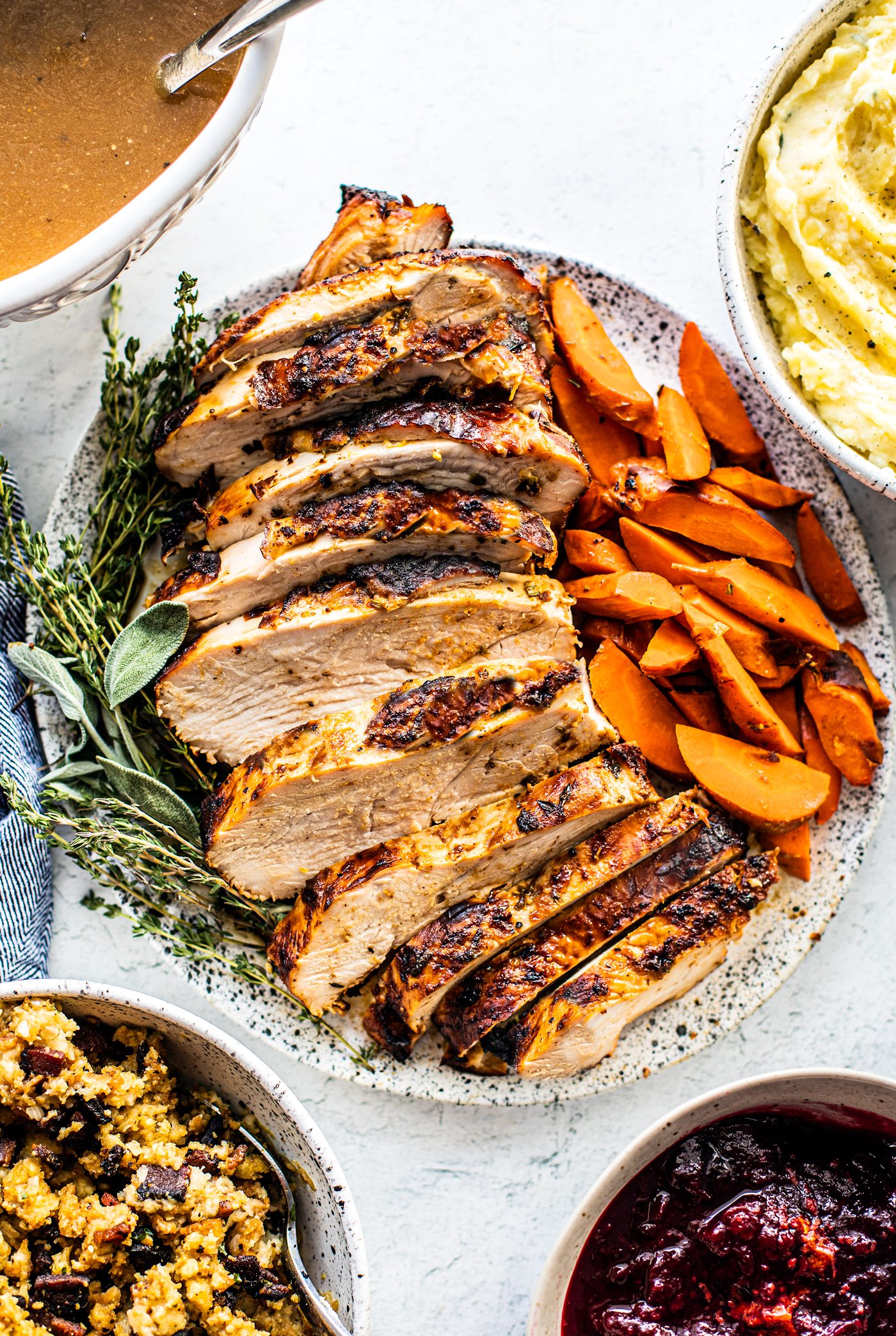 Sliced turkey breast on a serving platter with cooked carrots and fresh herbs.