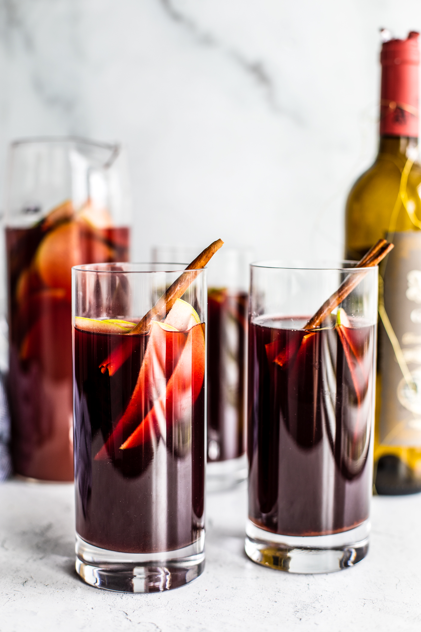 Two tall glasses of sangria with sliced green apples and cinnamon sticks in it.