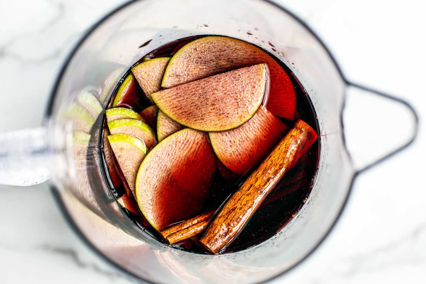 Overhead shot of pitcher full of red sangria, sliced green apples, and cinnamon sticks.