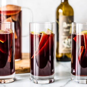 Three tall glasses of red sangria with sliced green apples and cinnamon sticks in it.