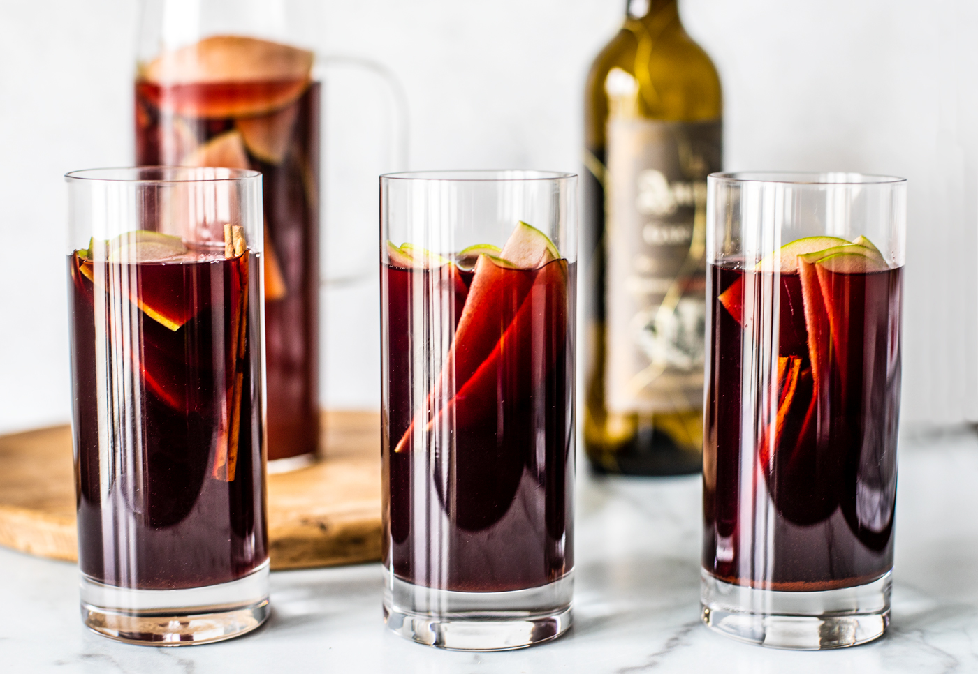 Three tall glasses of sangria with sliced green apples and cinnamon sticks in it.
