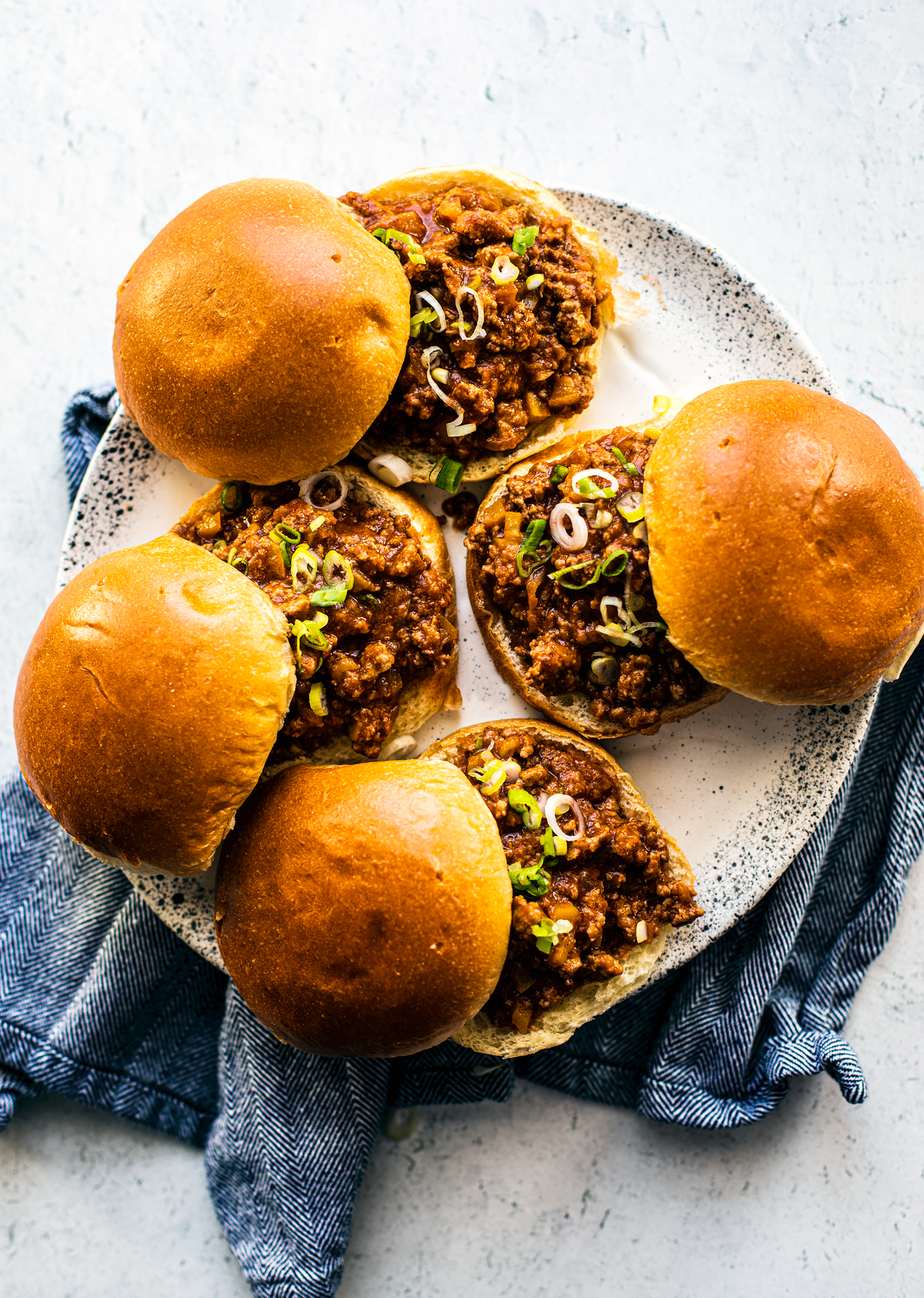 Sloppy Joes on a serving platter with a blue hand towel beneath it.