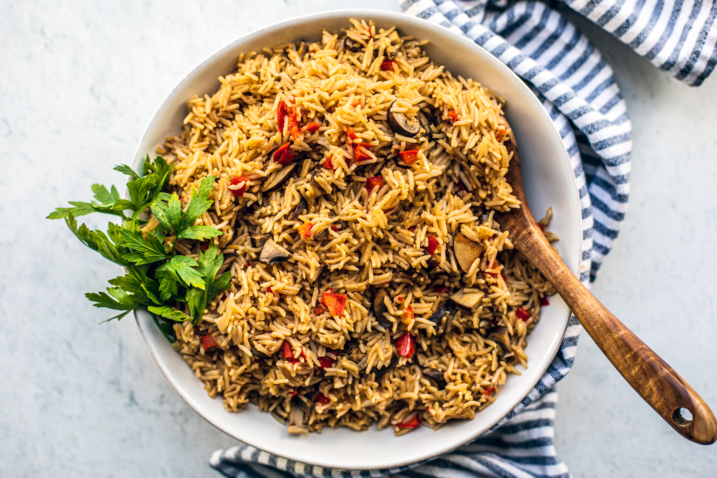 Serving bowl full of rice pilaf with a wooden spoon and blue and white striped hand towel underneath.