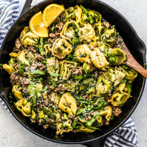 Cast iron skillet with tortellini and sausage, with a serving spoon in it.